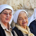 Two elderly nuns leaning against a stone wall and looking at the goings on