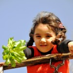 Little gitl with pigtails and red sweater vest, holding a leafy branch and looking down beyond the railing at the camera