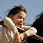 A little girl with dark hair looking down at something interesting and smiles
