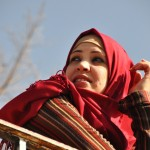 A Muslim lady in red head cover leaning against a railing and looks off into the distance