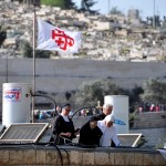 Three nuns and a priest on a roof with solar powered water heaters and flags carrying the Jerusalem Cross, observing the Catholic Palm Sunday Procession in 2015