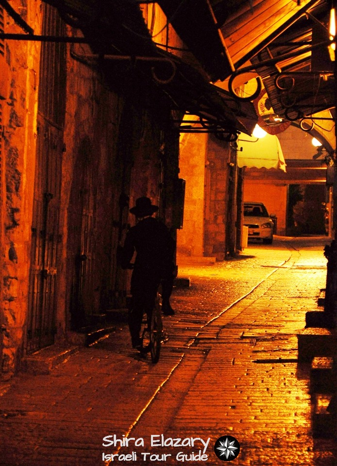An Orthodox Jew is seen from behind riding his bicycle through the street-light lit ally of the Old City of Jerusalem