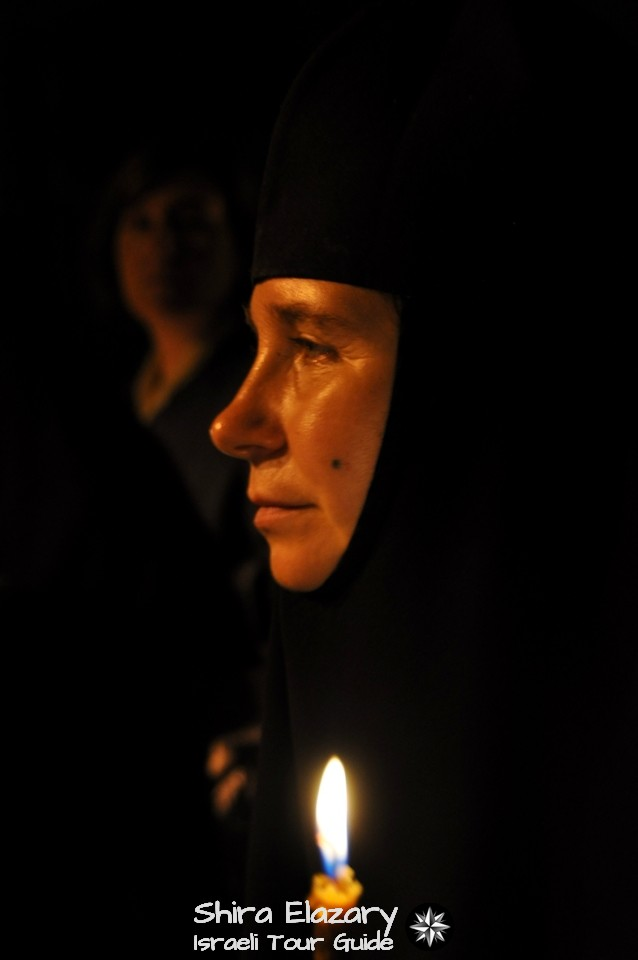 Profile of a Russian Orthodox nun with a lit candle, lighting the darkness around her