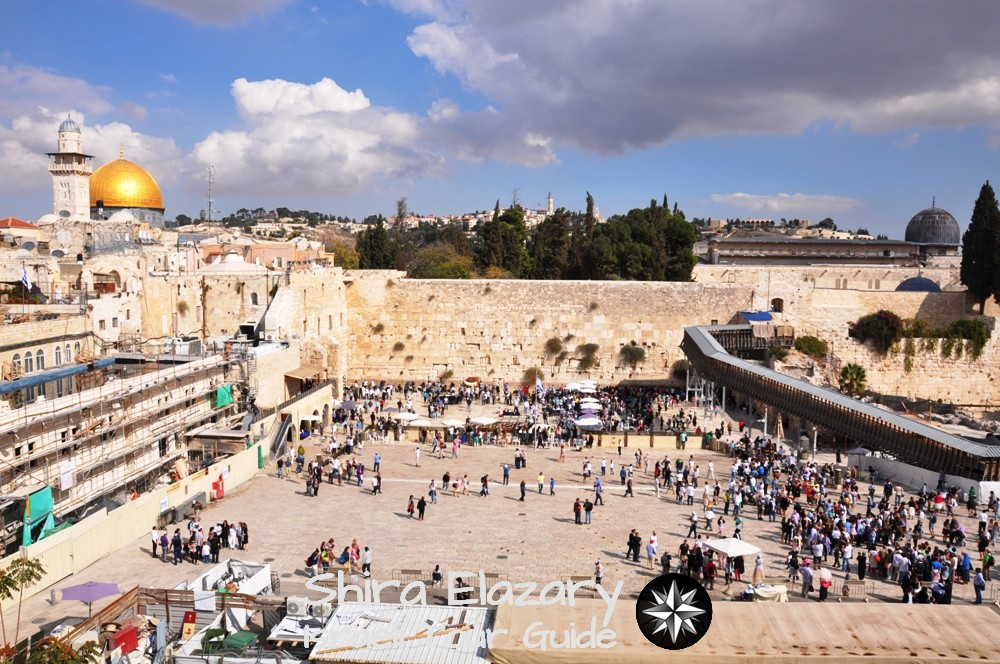 A wide view of the Western Wall of Temple Mount with the golden Dome of the Rock and many visitors on a bright afternoon