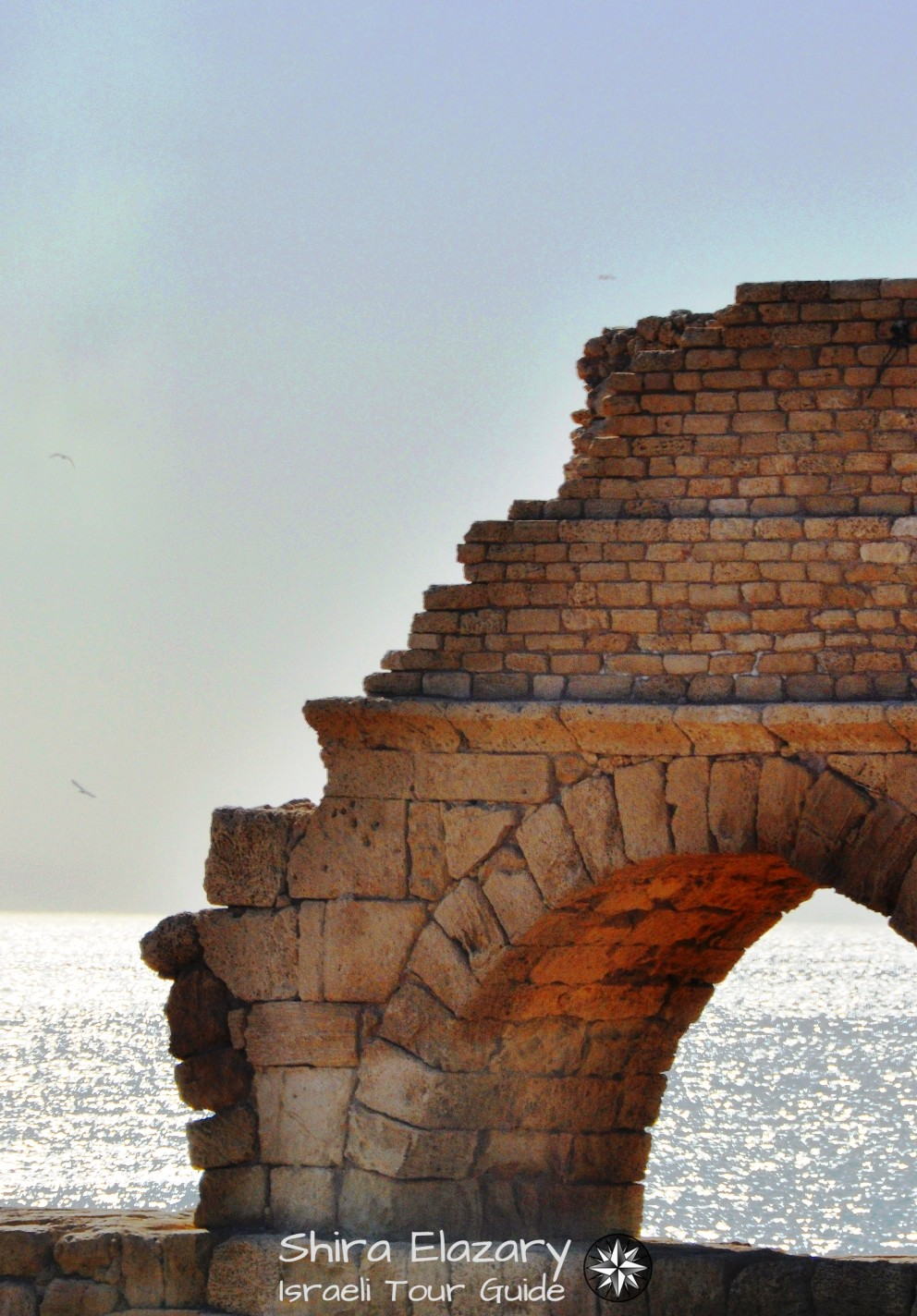 Caesarea's northern aqueduct at sunset with the sea behind it on a coastal area private tour
